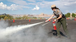 Ranger using a fire extinguisher on a roadway