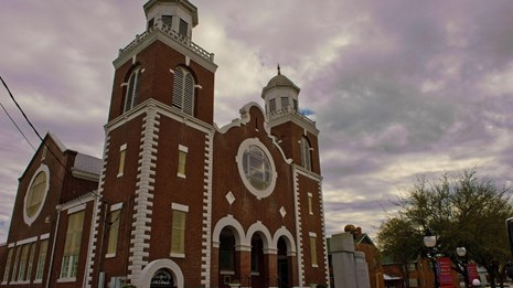 Large red brick church with two spires