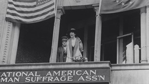 Black and white historic photo of two suffragists on a balcony