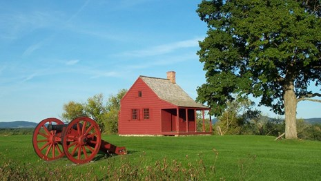 Cannon and historic barn in a field