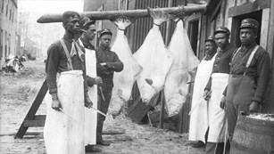 Historic black and white photo of a group of Black soldiers preparing halibut