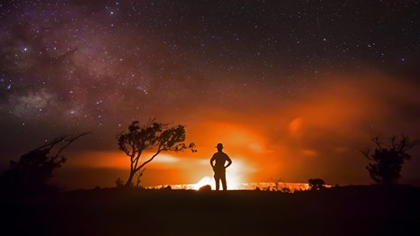 Silhouette of person against a lava eruption at night