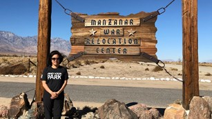 Kim Hirose Tobe standing in front of a sign for Manzanar War Relocation Center