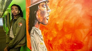 Park Ranger Elijah Prince standing next to his painting of a ranger