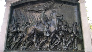 Bas-relief of a soldier on horseback riding along a line of marching soldiers
