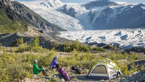 Two campers with tents near the base of a glacier