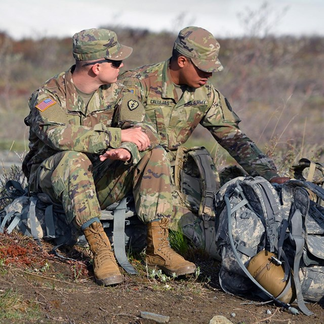 Two army soldiers sitting on ruck sacks