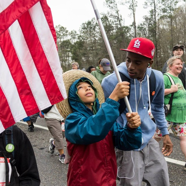 Man talking to a child holding a US flag as they march in the street