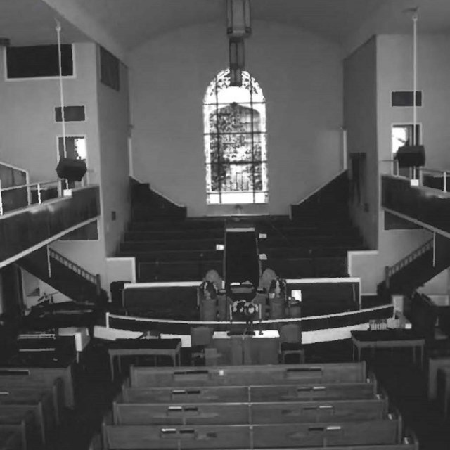 Historic black and white photo of the inside of a church