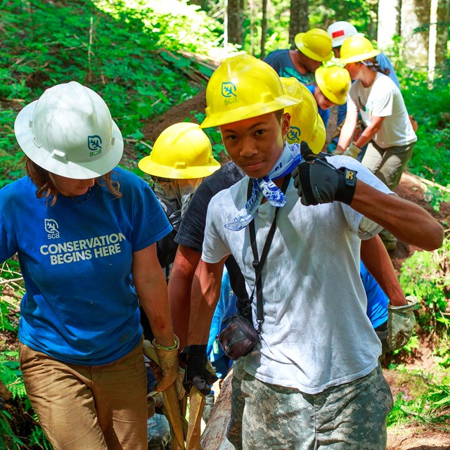 Group of youth wearing hardhats walking on a trail