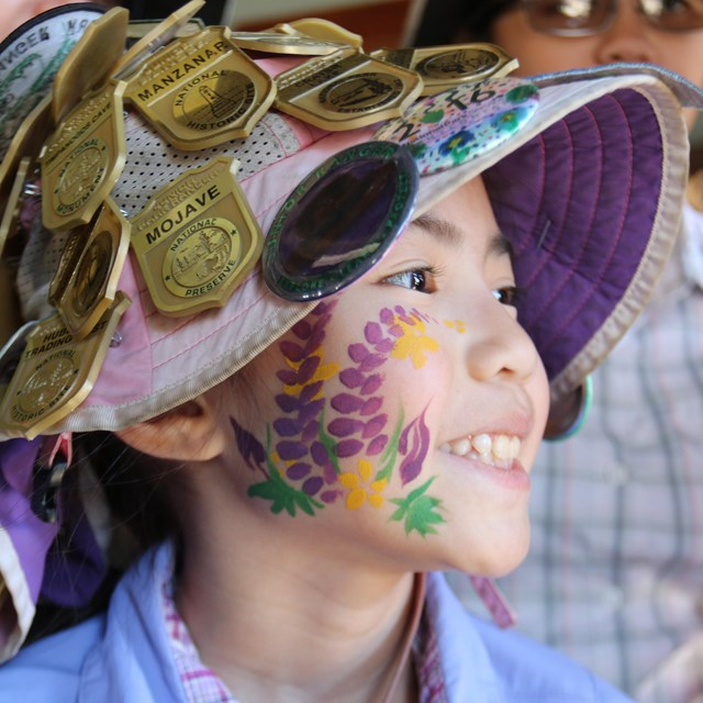 Kid with face paintings wearing a hat covered in Junior Ranger badges