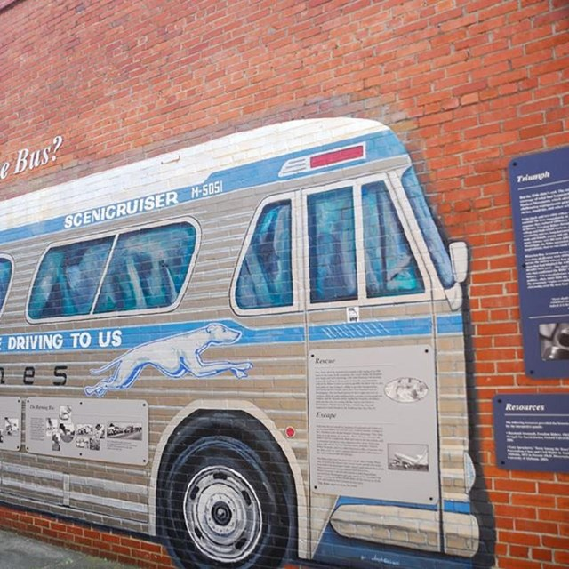 Mural of a Greyhound bus on a brick wall