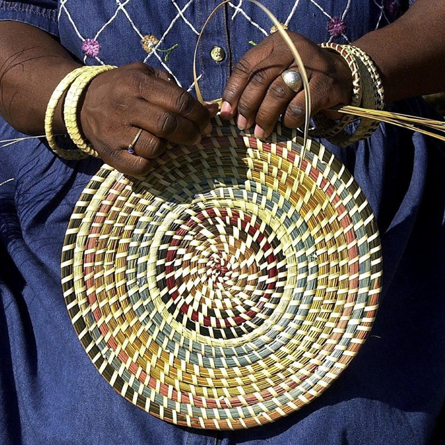 Hands weaving a colorful basket