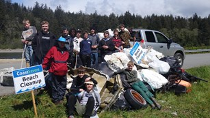 Volunteer group posing on beach with collected marine debris.