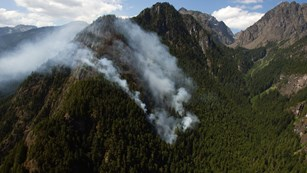 Smoke from a wild fire drifts up from a forested ridge.