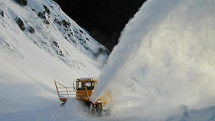 Snow plow blows snow up and out of the way.