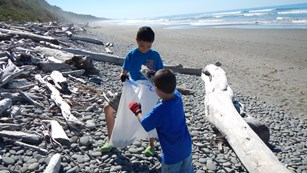 Young boys picking up marine debris on a beach.