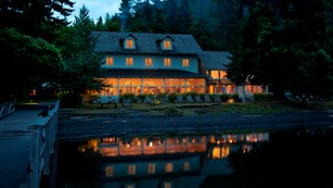 Lake Crescent Lodge lights reflect upon the lake in evening.