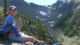 Hiker rests along a mountain trail.