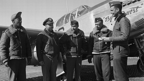 Col. Benjamin Oliver Davis presents a war bond to four airmen in front of a fighter jet, 1945