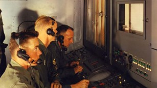 Uniformed operators with headsets seated in Nike Hercules battery control trailer, 1959.