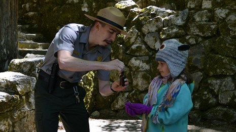 Oregon Caves park ranger using acid on marble to show a child how the caves were formed.