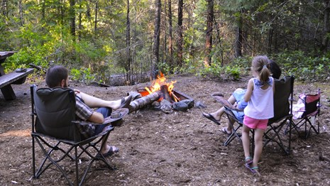 Three people sitting around a campfire at Caves Creek Campground.