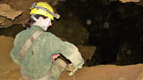 Off trail caver in jumpsuit and hard hat sitting on cave floor and holding a rope.