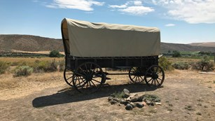 A covered wagon in a desert setting.