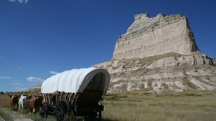 A large covered wagon in front of a towering sandstone bluff.