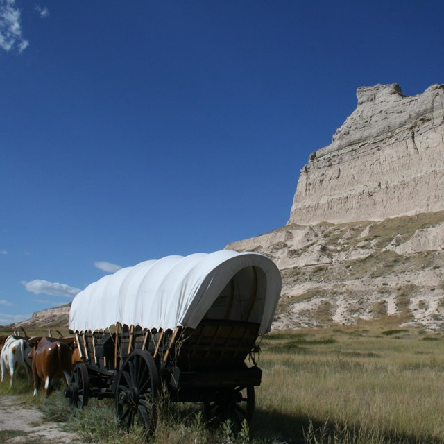 A covered wagon in front of a large sandstone bluff.