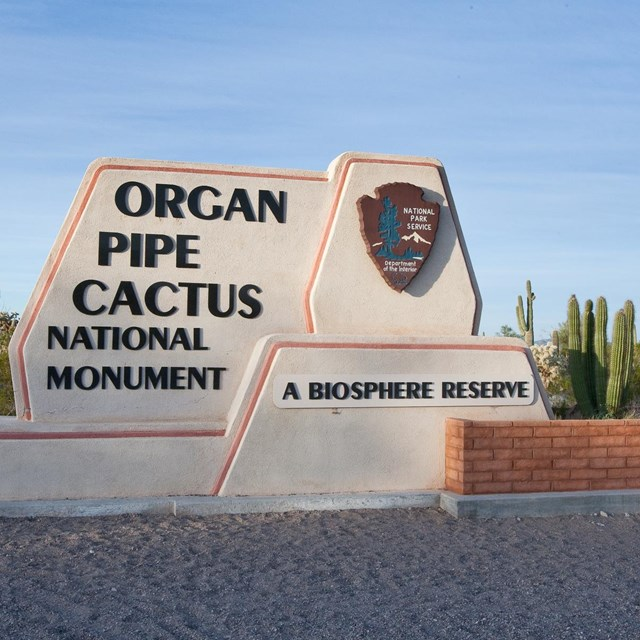 entrance sign to the monument, with NPS arrowhead and organ pipe cactus