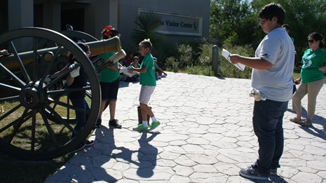 A Park Stewards Summer Intern and children standing at a cannon.