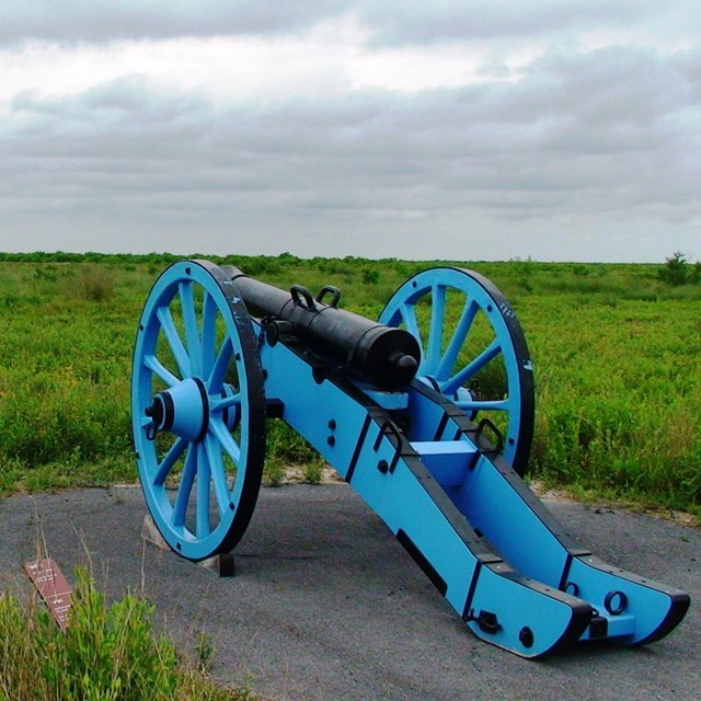 Replica cannon with a blue carriage overlooking the battlefield.