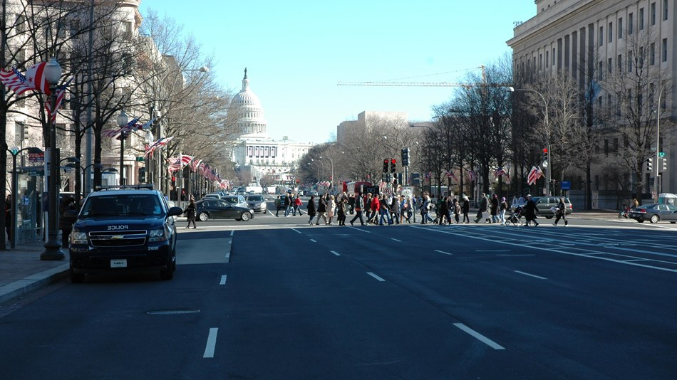 People walking across Pennsylvania Ave
