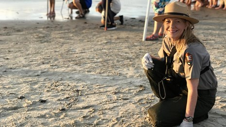 A female NPS ranger kneels on the beach with baby sea turtles crawling next to her.