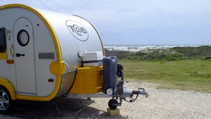 Silver and yellow camping trailer on the left with the beach visible in the distance.