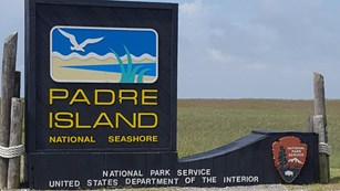 Park entrance sign with simple painting of bird flying over the beach.