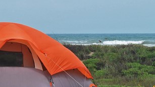 Orange tent pitched in front of dunes with Gulf of Mexico in background