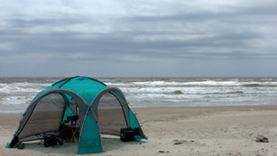a green tent rests on the beach with the Gulf in the background
