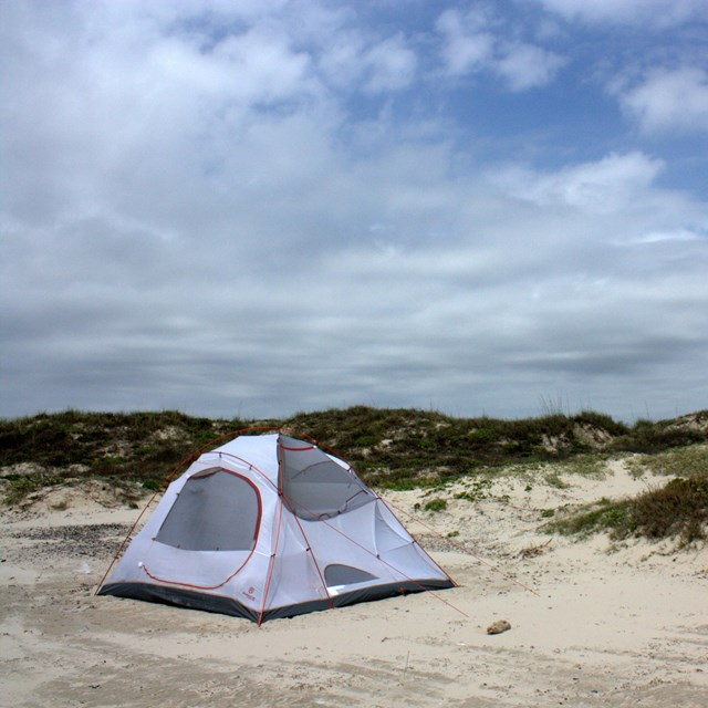 White tent on the beach with vegetated dunes behind and a cloudy-blue sky above.