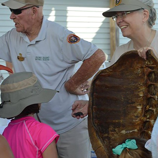 Two volunteers stand in front of a group of people, one volunteer is holding a sea turtle shell.