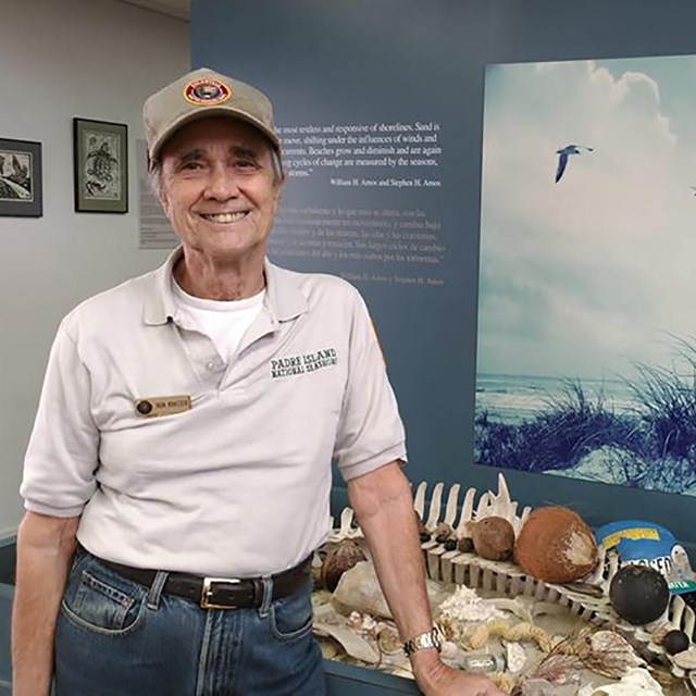 A volunteer smiles at the camera as he stands in front an exhibit in the visitor center.