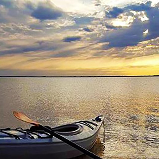 A kayak rests partly on shore on the left in calm water with a blue and yellow sunset sky above.