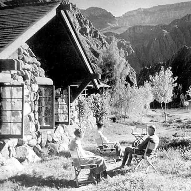 A black and white historic photo of people by a cabin in a park.