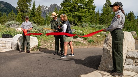 NPS Rangers hold red ribbon aloft against backdrop of mountains & trees. Ribbon is being cut.