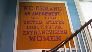 a women's suffrage banner hangs in a staircase at Belmont Paul Women's Equality National Monument