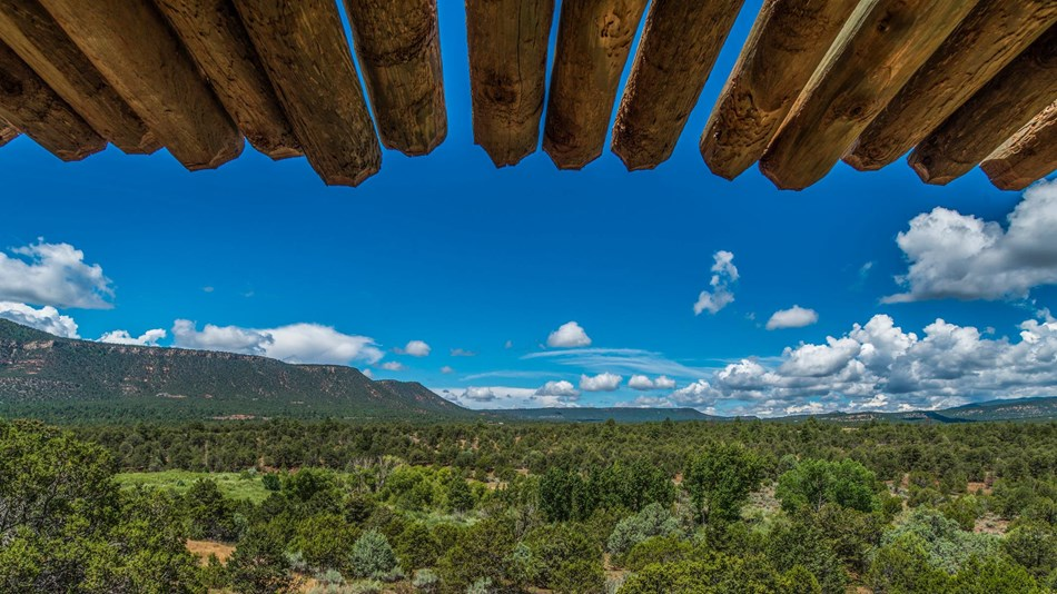 Wooden beams from the ramada frame view of mountains surrounding Glorieta pass.