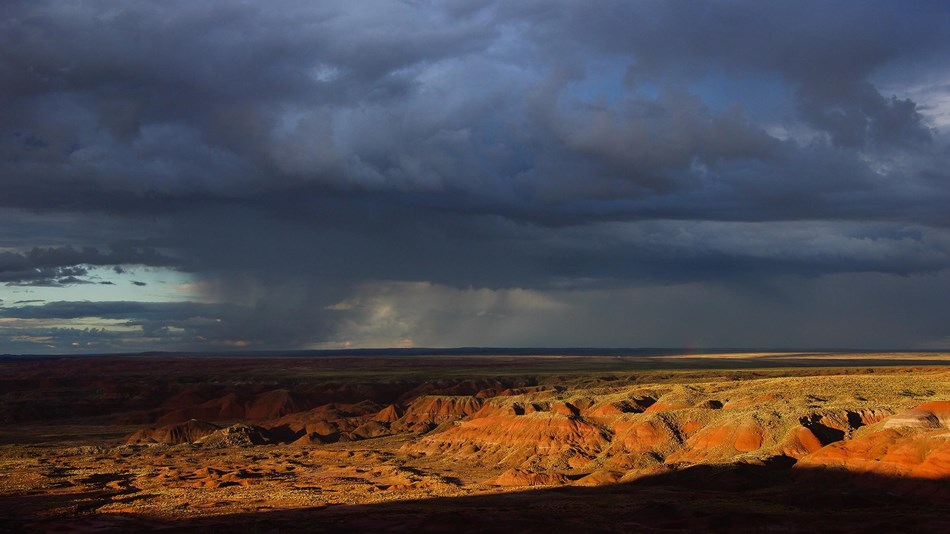 Dark thunderheads above sunset lit badlands.