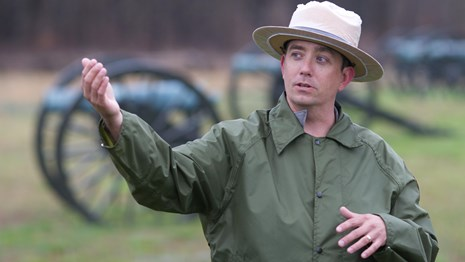 Photo of a National Park Rangers in a ranger hat and ranger rain coat talking about the battle.